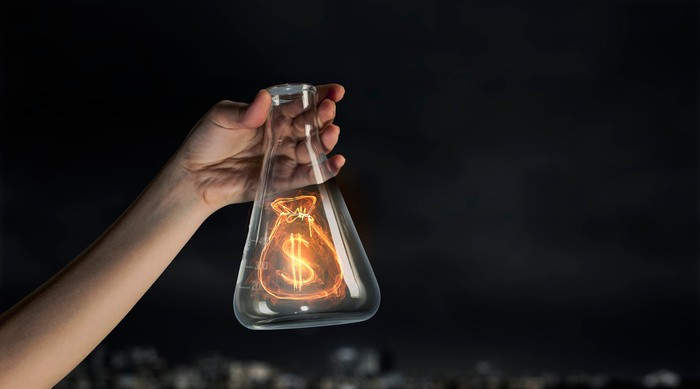 A hand holds up an Erlenmeyer flask with an icon of a golden money bag inside.