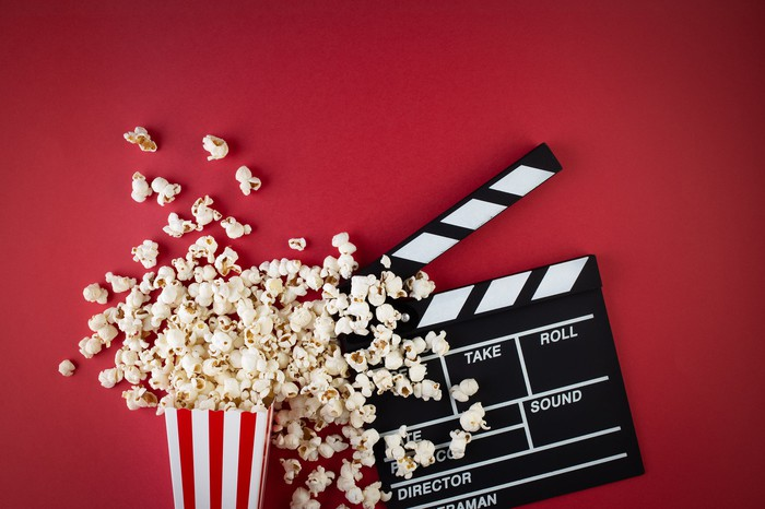 A popcorn box spilling over and a film slate.