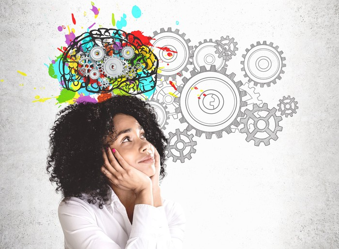A woman looks up at a drawing of gears beside a brain.