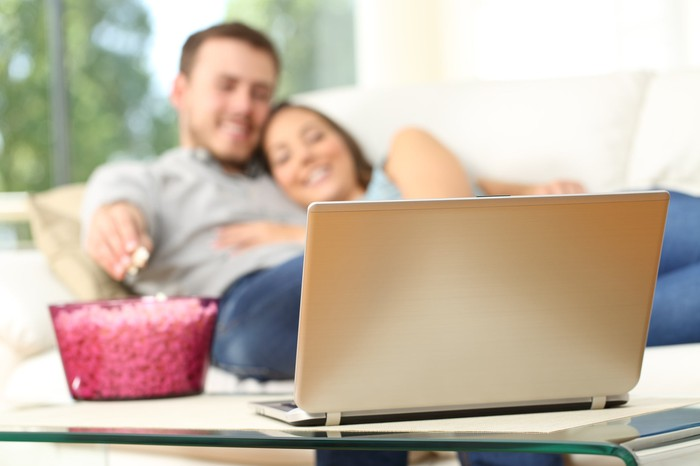 A man and a woman reclining on a couch while eating popcorn and looking at a laptop.