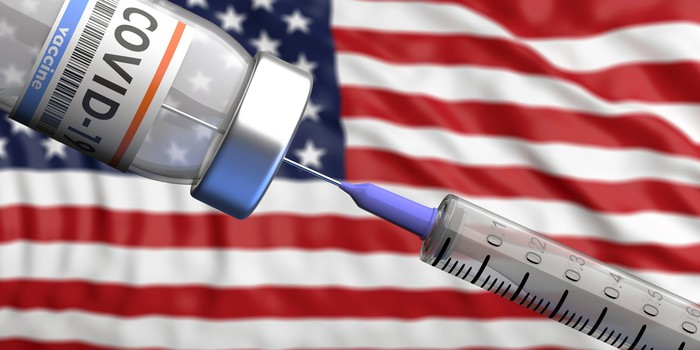 COVID-19 vaccine is drawn up in front of an American flag.