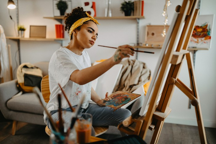 Seated young woman holding a paint brush while considering her easel-supported canvas.