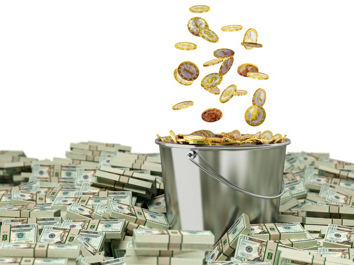 Coins falling into a bucket surrounded by piles of cash