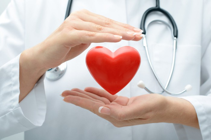 A doctor's hands hold a heart shape in front of her white coat.