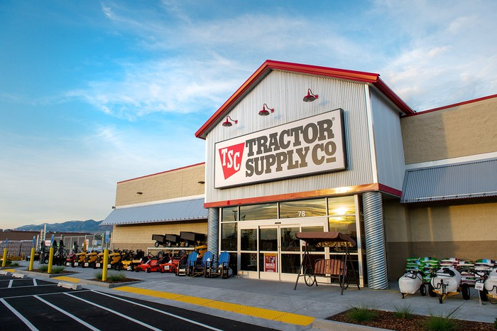 A Tractor Supply Company storefront, illuminated by morning light with a partly cloudy sky above.