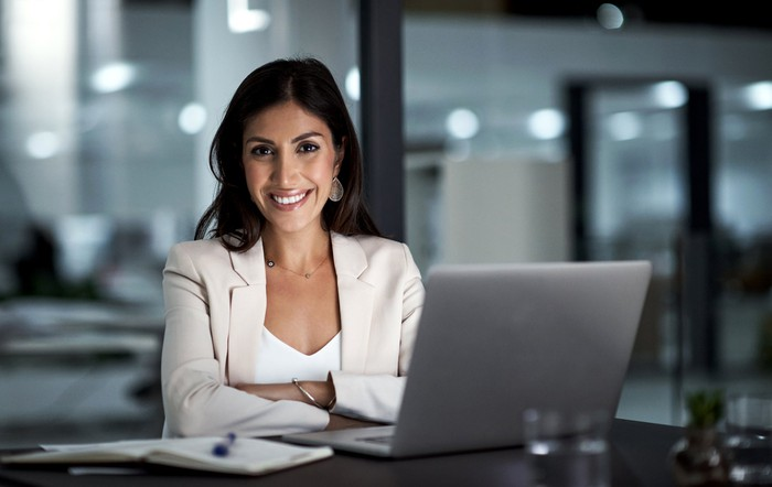 Smiling professionally dressed person at a laptop.