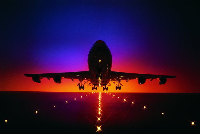 Airplane with landing gear just above a lit runway at sunset.