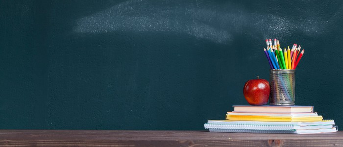 In front of a blackboard, an apple and cup of pencils sit on a stack of books.