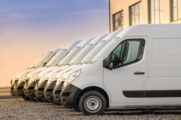 A side view of a fleet of white light commercial vans.