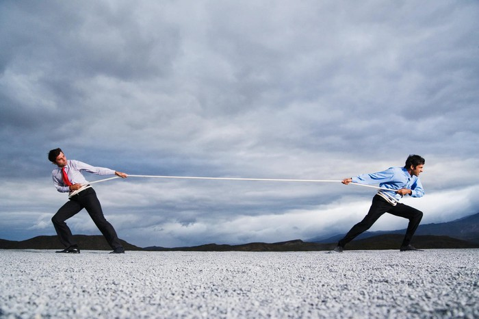 Two people in shirt and tie doing a tug of war with a rope in a desert landscape.
