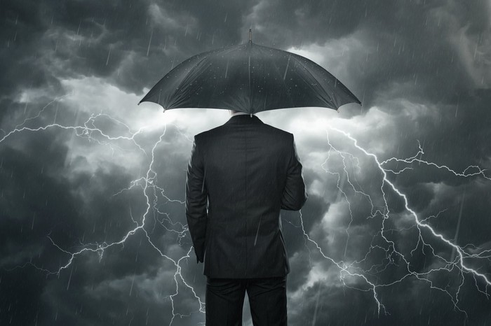 A businessman stands under his umbrella, watching the rain and thunderclouds around him.