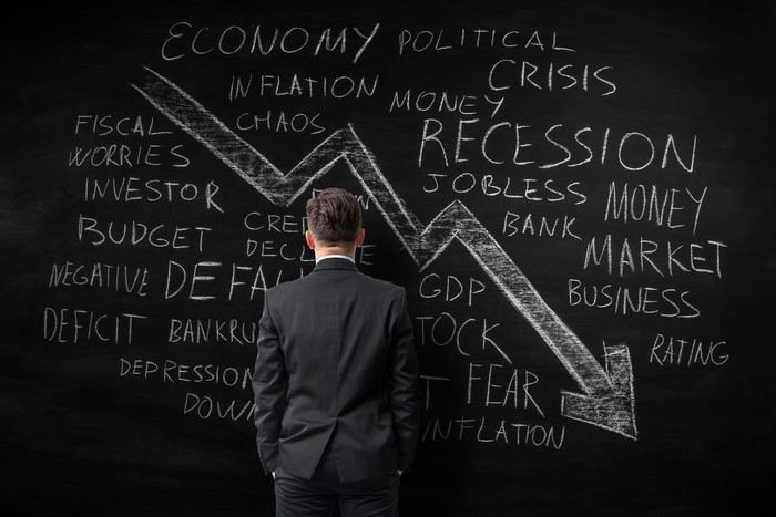 A man stares at a chalkboard with many reasons the stock market would fall and a large arrow pointed down and to the right.