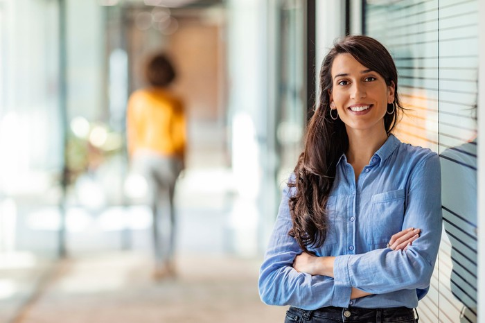 A woman, who is a financial advisor, standing in front of her office, smiling, with her arms folded, ready to help.
