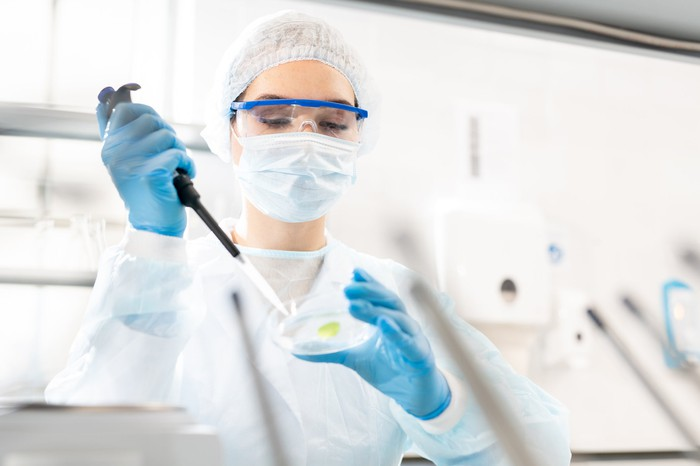 A researcher studying a sample in a petri dish.