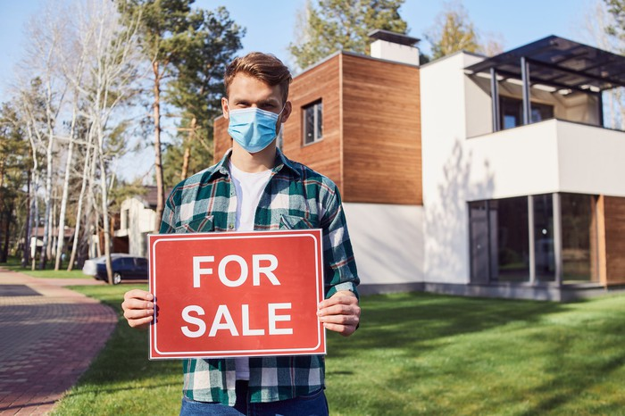 """Young man wearing a health mask holds a """"For Sale"""" sign in front of a house."""