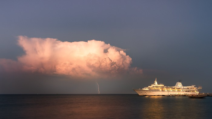 Lightning bolt from approaching storm near cruise ship
