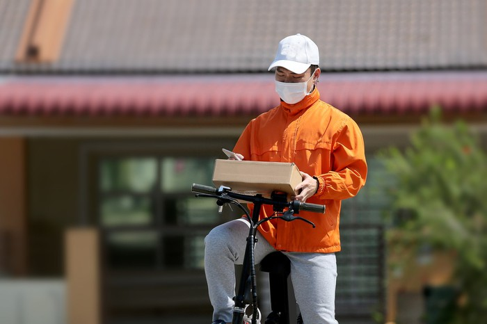 A deliveryman on a bike looks at a package in hishands wearing a mask.