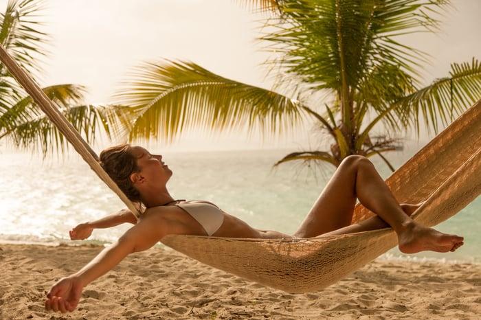 A woman in a hammock on a beach.
