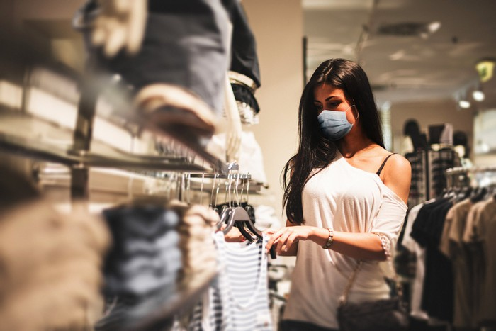 A young woman wearing a mask shops for clothing.
