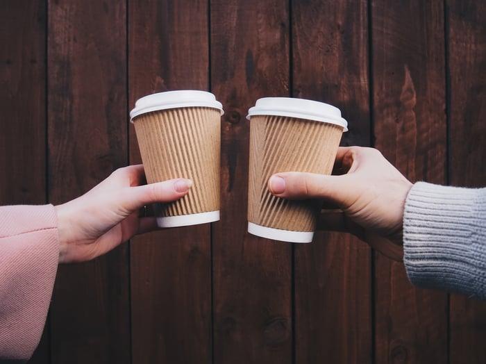 Deux personnes brandissent des tasses de café sur un fond de panneau de bois.