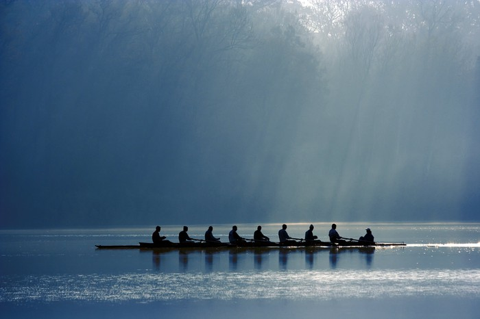 Crew rowing a boat down the river