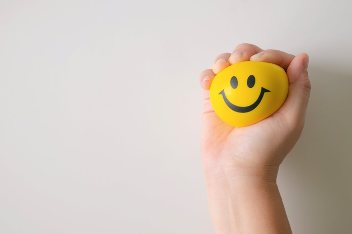 A hand squeezes a ball with a smiley face on it.