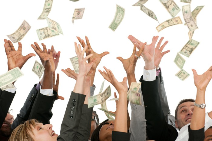 A group of people dressed in suit reaching for falling money.