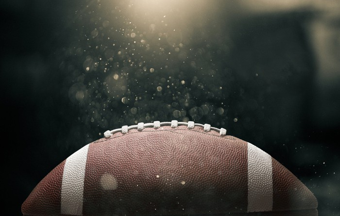 American football ball on black background illuminated.