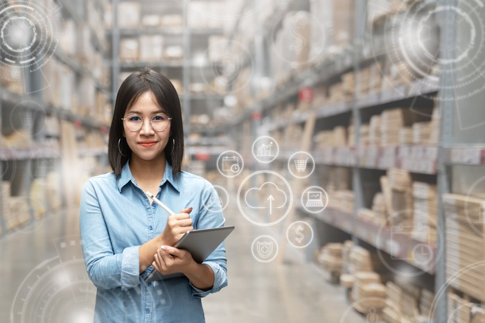 Smiling woman holding a clipboard inside a warehouse.