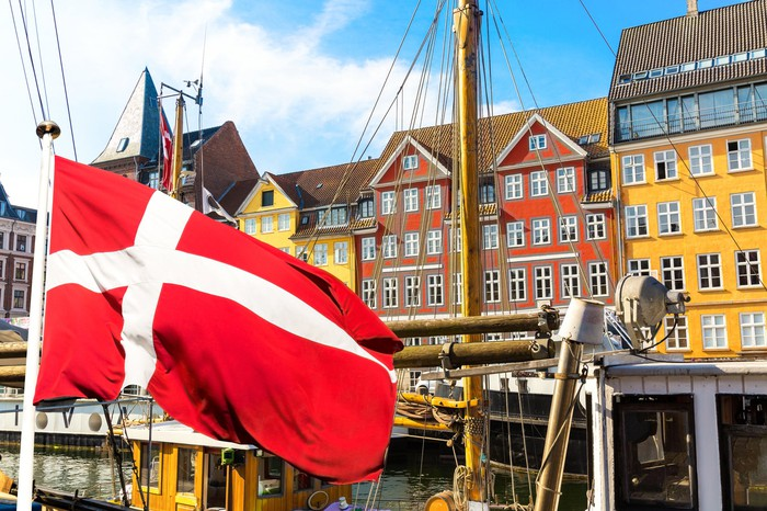 Colorful houses in Copenhagen, Denmark, with a Danish flag in the foreground.