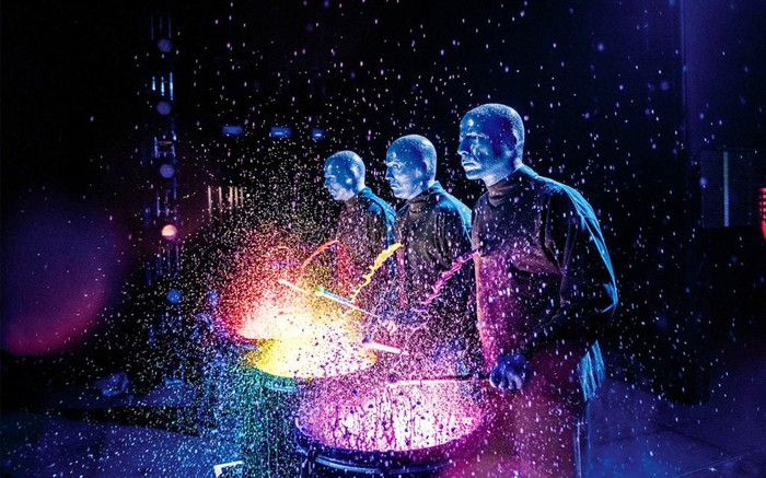 Three Blue Man Group performers playing drums in colored water.