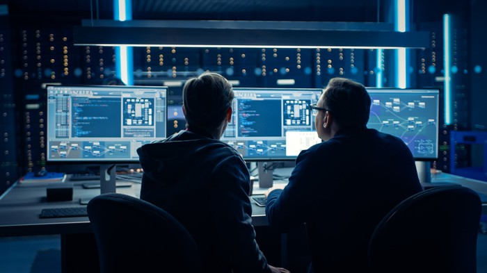 Two employees looking at a myriad of data on multiple computer monitors.