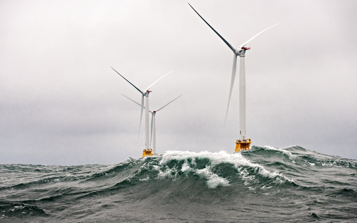 Three offshore wind turbines in heavy seas.
