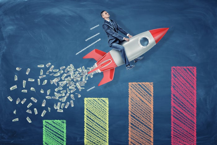 A businessman riding a rocket ship expelling cash exhaust flies over a multi-colored bar chart.