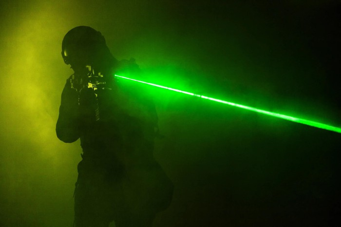 Person holding gun with green laser sight.