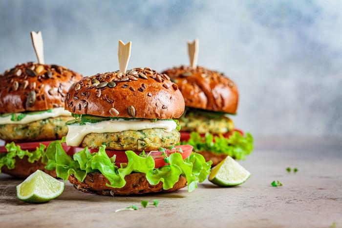 Three vegan burgers sitting in a triangle