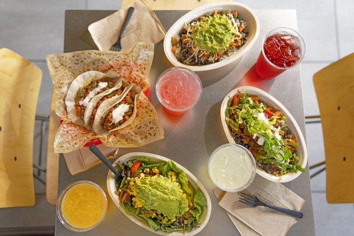 A table full of Chipotle food items and drinks.