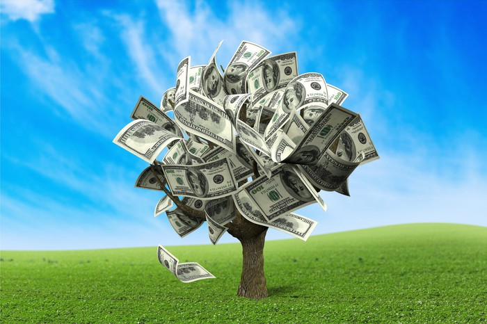 A tree made of money stands in a field.