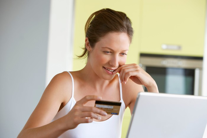 A smiling woman holding up a credit card in her right hand, with an open laptop on the table in front of her.