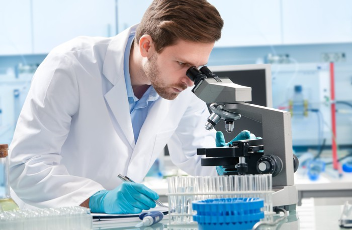 Scientist looking through microscope in lab.