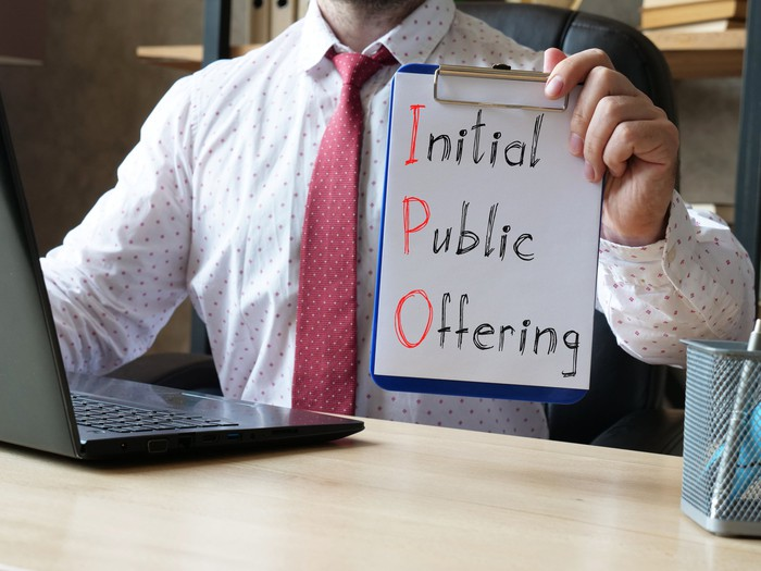 """A man sitting at a desk in front of a computer holding a clipboard that reads """"initial public offering"""" with the letters """"IPO"""" highlighted."""