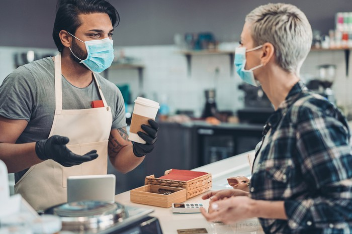 Masked barista handing cup of coffee to masked customer
