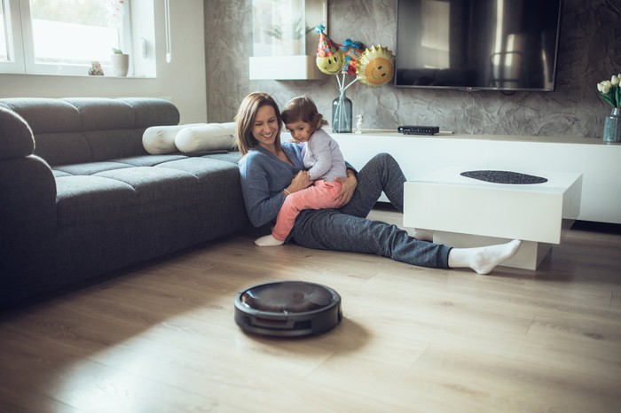 A mother and daughter looking at a robot vacuum cleaner.