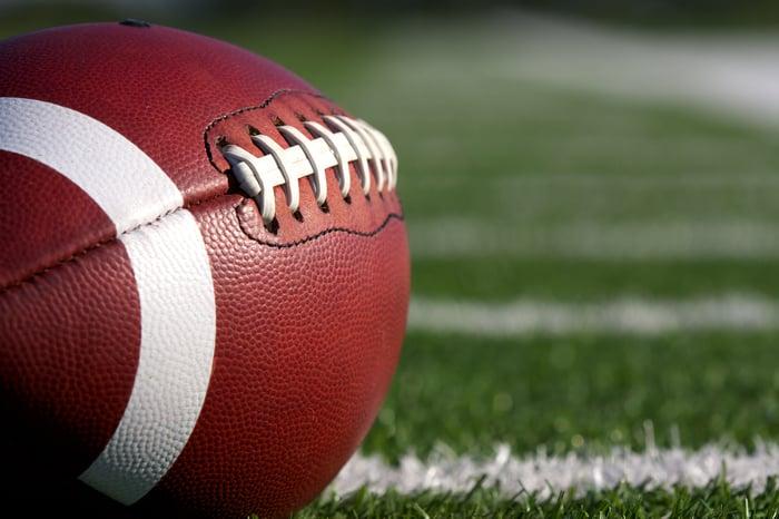 An American football sitting on a football field.
