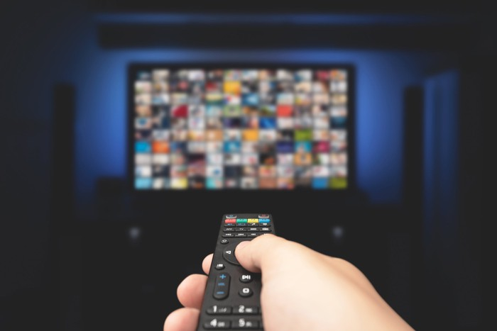 A man holds a remote control in front of a TV screen.