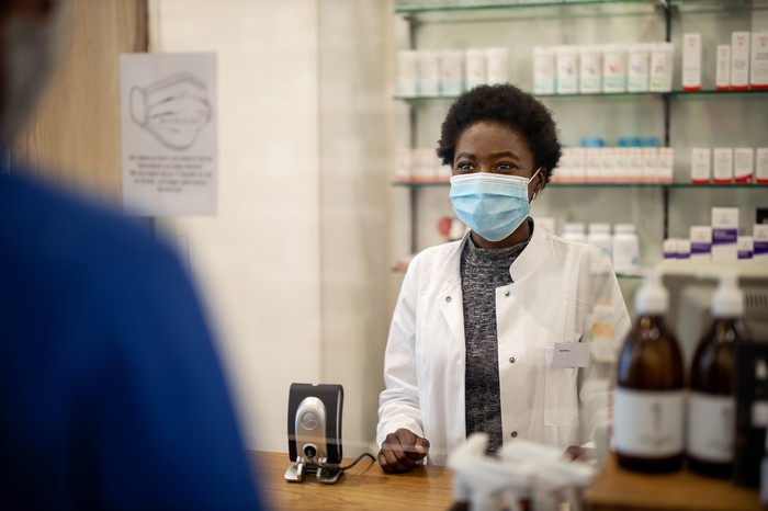 Female pharmacist wearing a mask and white coat stands behind a counter, in front of a wall of white pill bottles, greeting customer in blue shirt.