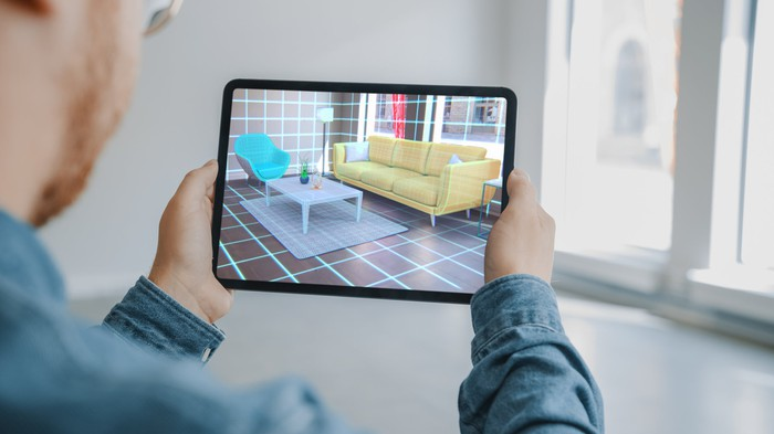 A person using a tablet and augmented reality to envision a living room layout.