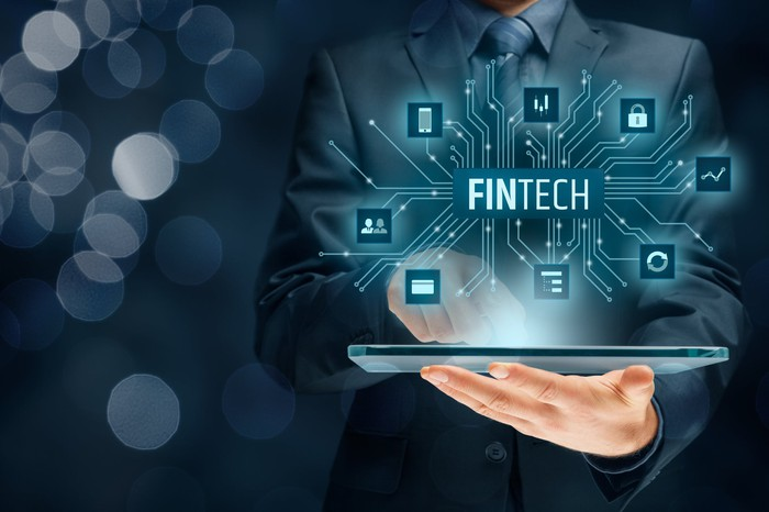 A person holding a tablet displaying icons and the word 'Fintech.'