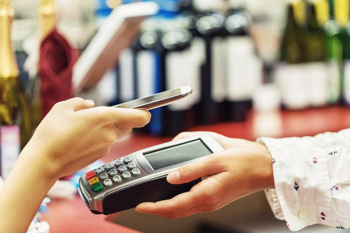 A customer uses a smartphone for contactless payment.