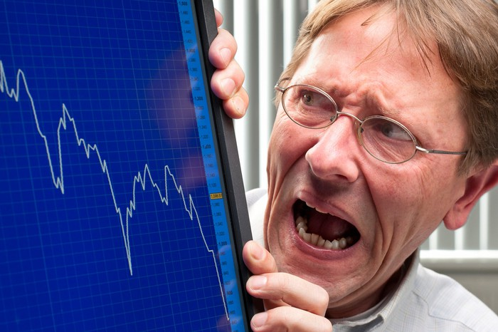 Horrified-looking man viewing falling stock chart on computer